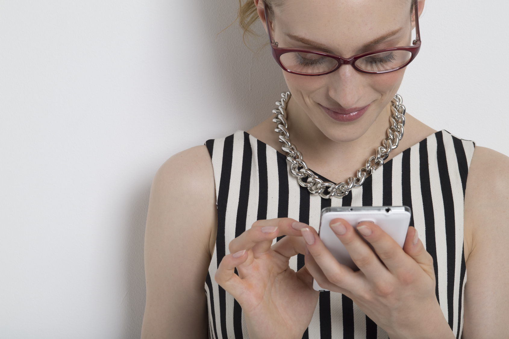 Woman looking at the mobile phone with a smile