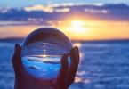 Die Sonne geht ber dem Bodensee unter und leuchtet durch eine Glaskugel.
