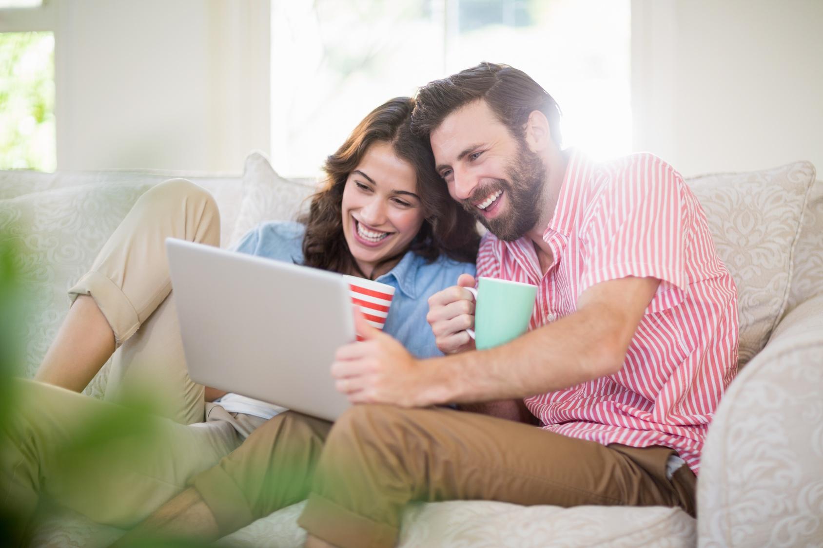 Couple sitting on sofa and using laptop