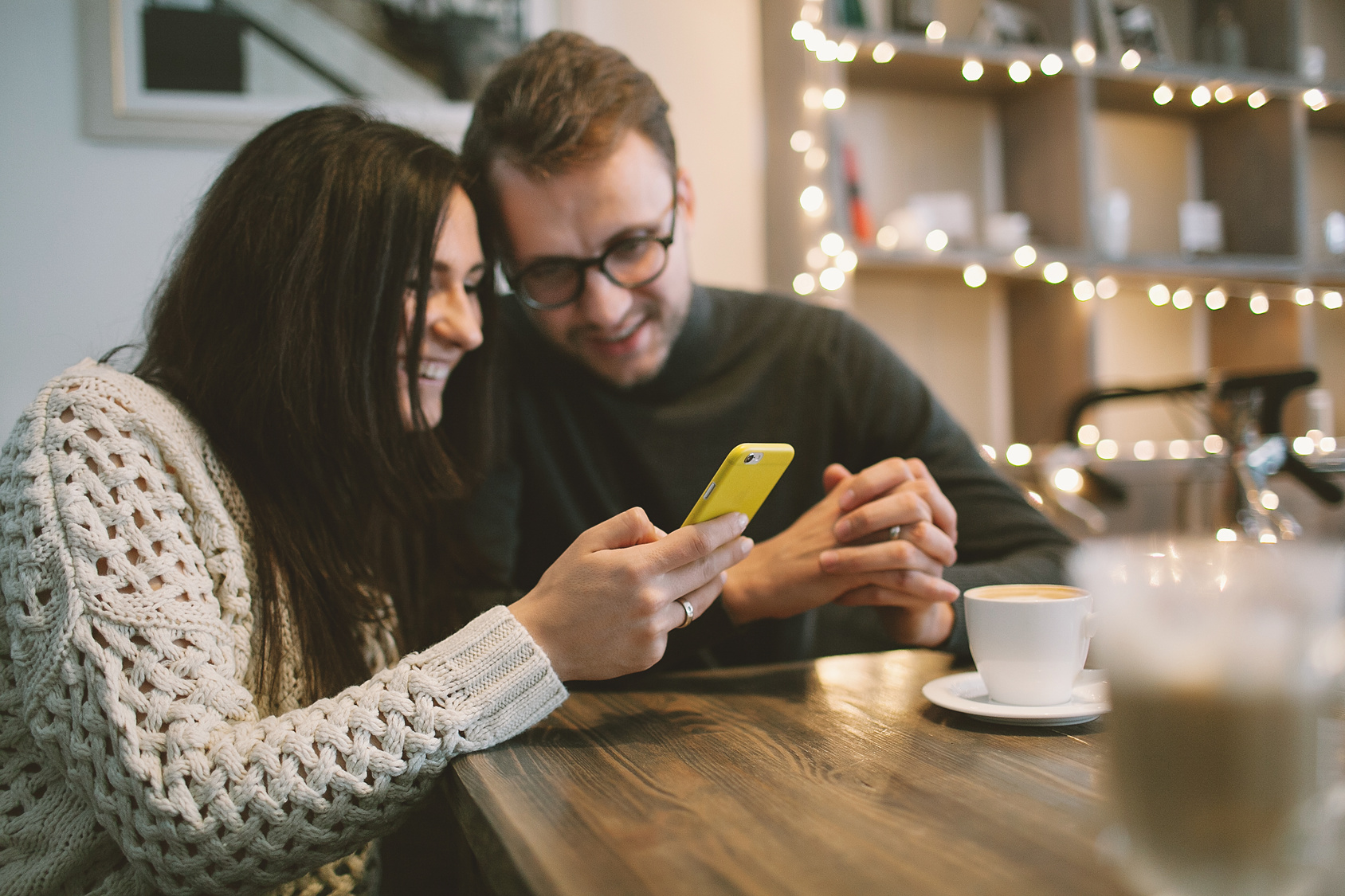 Young couple in cafe sitting with smartphone and coffee