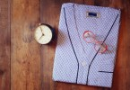 clean folded man's pajama, vintage clock and glasses over wooden background