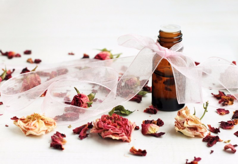 Dropper bottle with ribbon, essential oil, dried rose buds scattered white table.