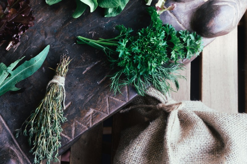Cooking ingredients - pepper, bok choy, thymus and parsley arranged at the canvas background