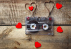 Audio cassette with magnetic tape in shape of hearts on wooden background