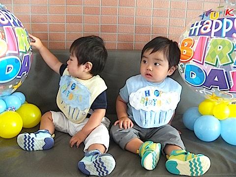 お揃いのスタイをした双子の赤ちゃん