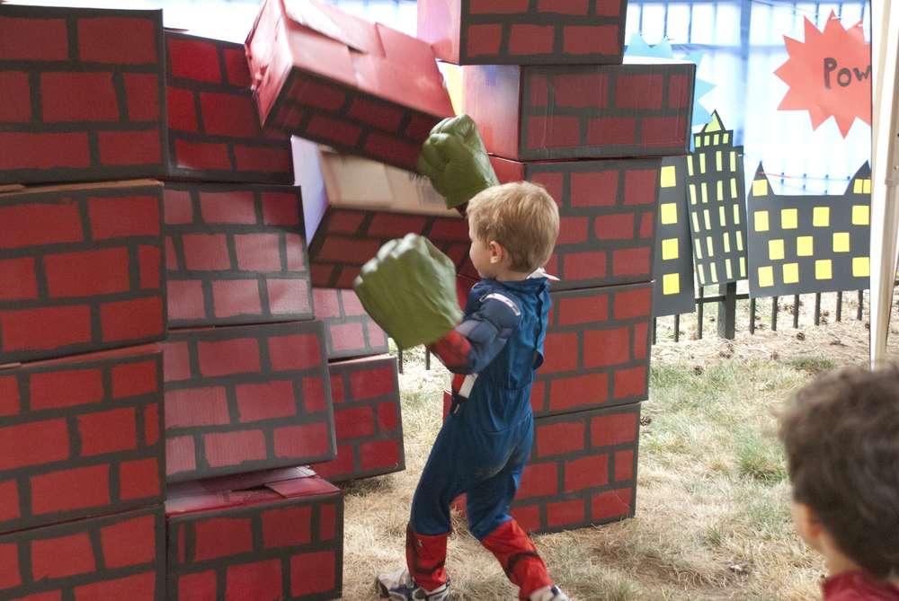 ダンボール箱で作ったレンガブロックをパンチする少年