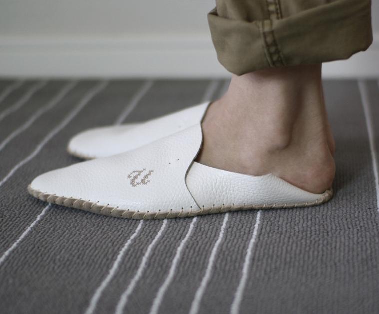 白い革製のルームシューズを履いた足元
